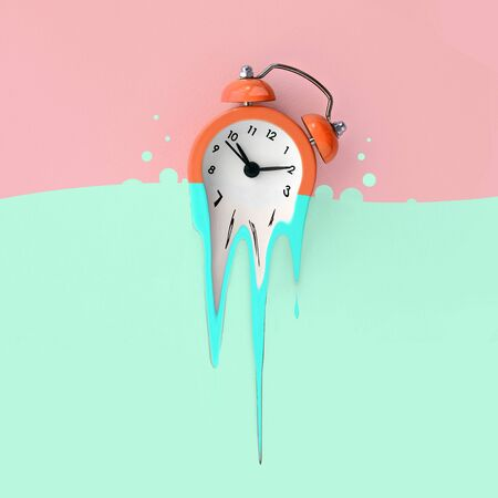 Time is running out concept shows alarm clock that is dissolving down by melting in pastel blue liquid substance . Surreal style image Imagens