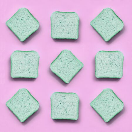 A few pieces of green bread lies on texture background of fashion pastel pink color paper in minimal concept.