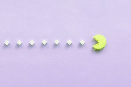 A composition of macaroon with an open mouth that is going to eat sugar cubes on a lilac pastel background. The concept of old video games.