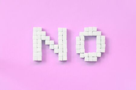 NO Letters of sugar cubes on a pastel pink background. Diabetic concept. Refusing sugar. Flat lay minimal top view