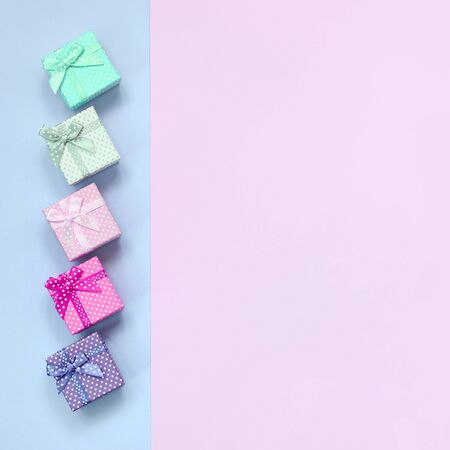 Small gift boxes of different colors with ribbons lies on a violet and pink color background.