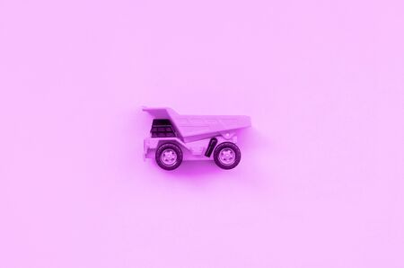 Small purple toy truck on texture background of fashion pastel purple color paper in minimal concept.