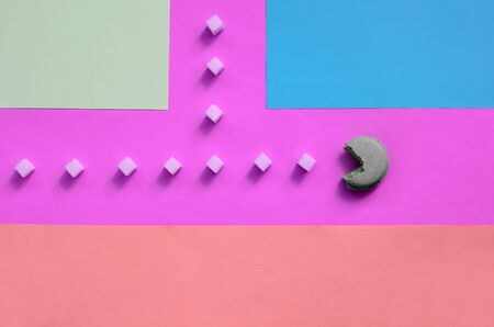 A composition of macaroon with an open mouth that is going to eat sugar cubes on a pink, lime, blue and coral pastel background. The concept of old video games. Banco de Imagens