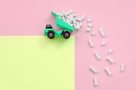Green little toy dump truck throws marshmallow pieces from its raised back on a pastel yellow and coral background. Flat lay minimal top view.