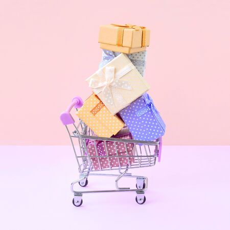 Many colorful present boxes in supermarket shopping cart on peach background. Gifts for winter holidays