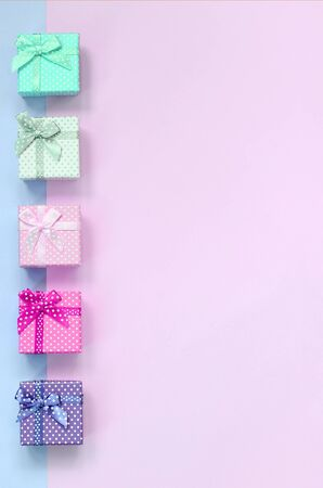 Small gift boxes of different colors with ribbons lies on a violet and pink color background. Imagens