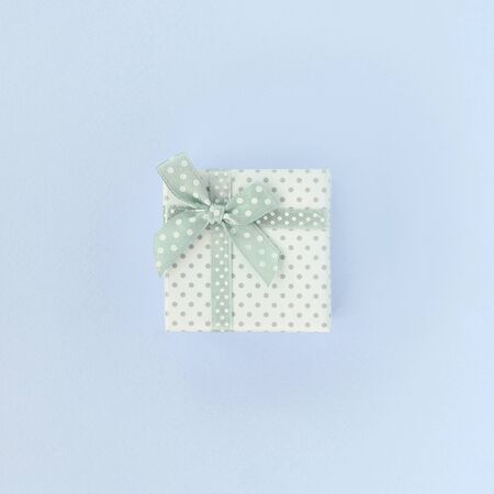 Small white gift box with ribbon lies on a violet background. Minimalism flat lay top view.