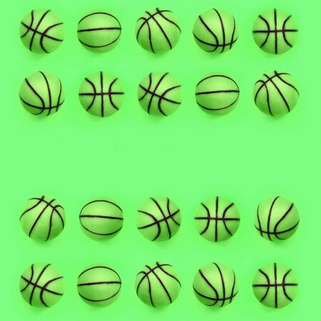 Many small green balls for basketball sport game lies on texture background of fashion pastel green color paper in minimal concept. Stock Photo
