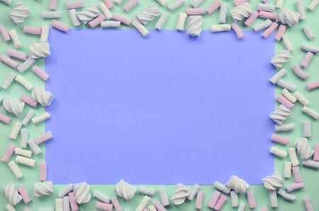 Colorful marshmallow laid out on green and lilac paper background. pastel creative textured framework. minimal. Stock Photo