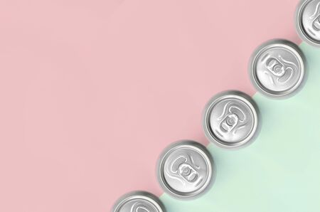 Many metallic beer cans on texture background of fashion pastel turquoise and pink colors paper in minimal concept.