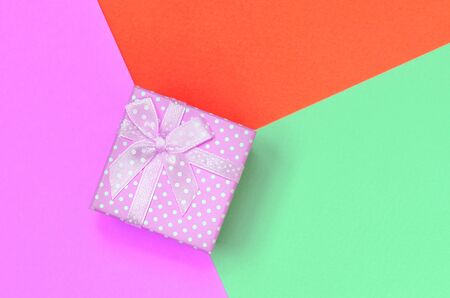 Small pink gift box lie on texture background of fashion pastel turquoise, red and pink colors paper in minimal concept. Stock Photo