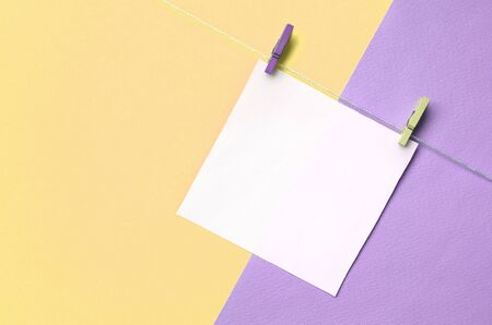 A piece of paper is hanging on a rope with pegs on texture background of fashion pastel yellow and violet colors paper in minimal concept