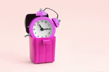 Wasting time concept. Pink alarm clocks in plastic trash bin on peach background. Bad and wrong time management