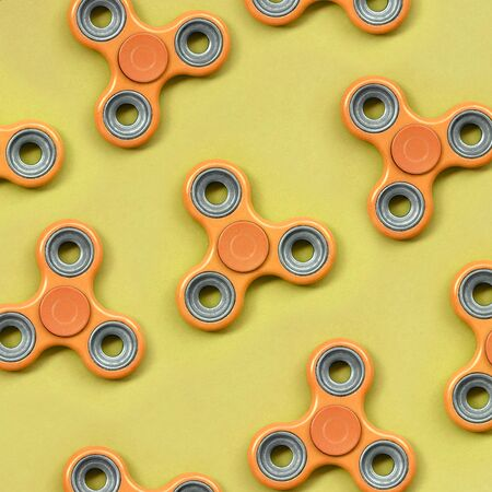 Many orange fidget spinners lies on texture background of fashion pastel orange color paper in minimal concept.