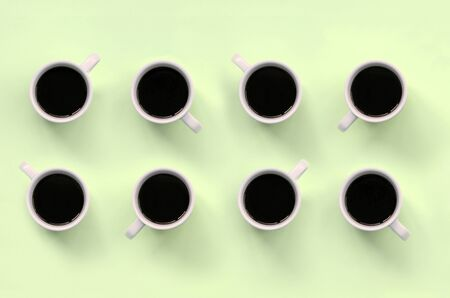 Many small white coffee cups on texture background of fashion pastel lime color paper in minimal concept.