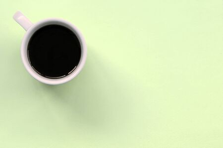 Small white coffee cup on texture background of fashion pastel lime color paper in minimal concept.