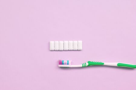 Toothbrush and chewing gums lie on a pastel pink background. Top view, flat lay. Minimal concept.