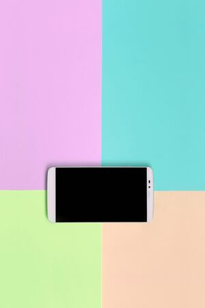 Modern smartphone with black screen on texture background of fashion pastel pink, blue, coral and lime colors paper in minimal concept.