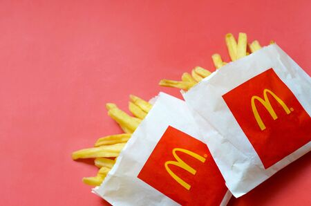 KHARKIV, UKRAINE - AUGUST 1, 2019: McDonald's French fries in small paperbag on bright red background. McDonald's Corporation is the world's largest and famous fast food restaurant