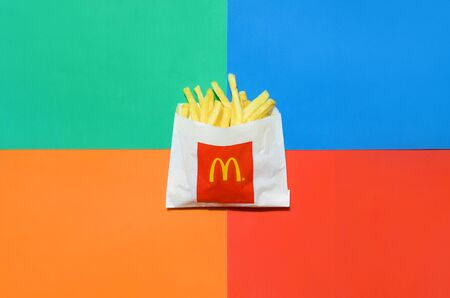 KHARKIV, UKRAINE - AUGUST 1, 2019: McDonald's French fries in small paperbag on bright colors mix background. McDonald's Corporation is the world's largest and famous fast food restaurant
