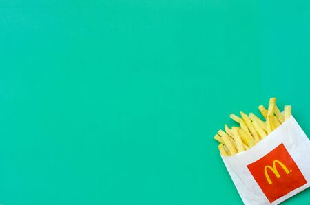 KHARKIV, UKRAINE - AUGUST 1, 2019: McDonald's French fries in small paperbag on bright green background. McDonald's Corporation is the world's largest and famous fast food restaurant Redakční