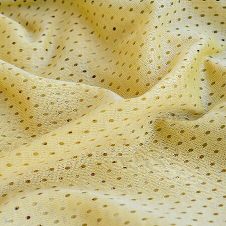 Yellow mesh sport wear fabric textile pattern background. Yellow color football jersey clothing fabric texture sports wear. Breathable porous poriferous material air ventilation with small holes Banque d'images - 129858405