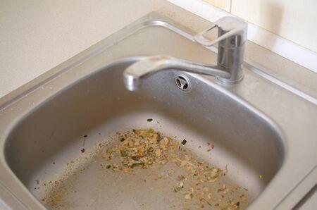 Primo piano sullo scarico del lavello da cucina sporco intasato. Sfocatura e messa a fuoco selettiva del foro del lavandino che si intasa con particelle di cibo Archivio Fotografico