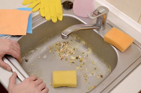 The housekeeper was faced with the problem of washing an overly dirty sink filled with food particles. Men hands lean on the unwashed kitchen sink