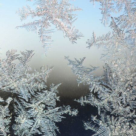 Snowflakes frost rime macro on window glass pane. Colorful ice on the window surface, natural background texture