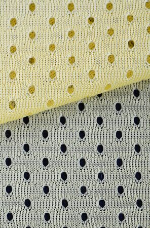 Yellow mesh sport wear fabric textile pattern background. Yellow color football jersey clothing fabric texture sports wear. Breathable porous poriferous material air ventilation with small holes