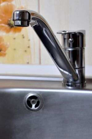 Empty clean silvery kitchen sink and water faucet close up indoors Reklamní fotografie