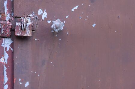 Closed metal lock garage door security protection padlock. Old brown gates with weathered peeling paint
