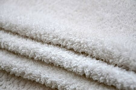 Close-up macro photo of a stack of many small white towels in daylight