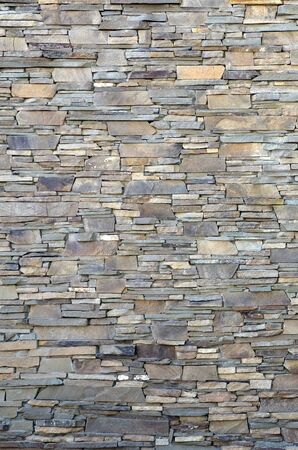 Modern pattern of flatten stone wall decorative surfaces in brown color. Stone lined with granite wall facing Stone rock