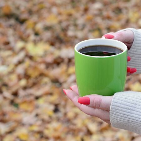 Woman wearing white sweater in their hands holding a green coffee cup in a relaxed mood on foliage background Reklamní fotografie