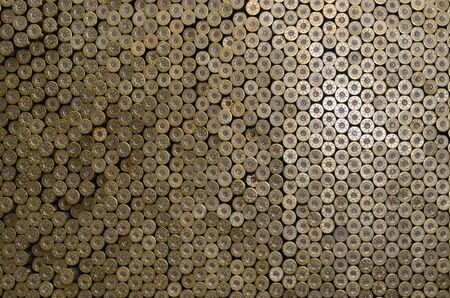 Pattern of 12 gauge cartridges for shotgun bullets. Shells for hunting rifle close up. Backdrop for shooting range or ammunition trade concepts. Used 12 caliber cylinder cooper caps in stack Фото со стока - 133477113