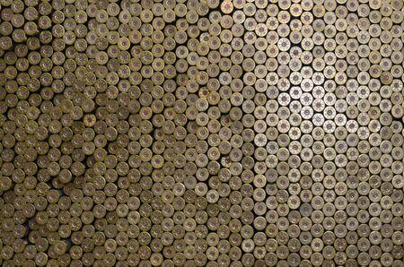 Pattern of 12 gauge cartridges for shotgun bullets. Shells for hunting rifle close up. Backdrop for shooting range or ammunition trade concepts. Used 12 caliber cylinder cooper caps in stack Reklamní fotografie