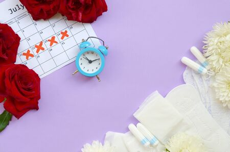 Menstrual pads and tampons on menstruation period calendar with blue alarm clock and red roses. Aspects of women wellness in monthlies period. Woman critical days gynecological menstruation cycle