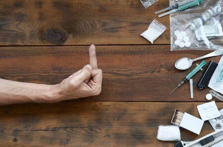 La mano masculina muestra el signo FUCK para todas las definiciones de sustancias narcóticas. Muchas pastillas de drogas y polvo sobre la mesa de madera. Luchar contra el abuso y el tráfico de drogas