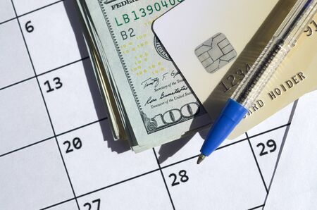 Pen and credit card on many hundred US dollar bills on calendar page close up. Business and financial planning concept. Accountant work