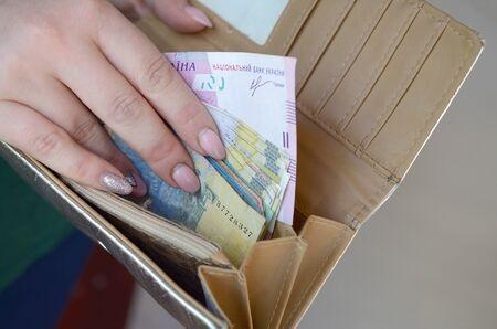 Female hands holding ukrainian hryvnia bills in small money pouch or wallet. Small salary in ukrainian economics concept. Poor life in ukraine 写真素材 - 132116599