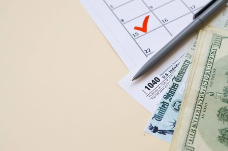 1040 Individual Income tax return form with Refund Check and hundred dollar bills on calendar with mark on 15th of april. Tax period concept. Financial planning and business 写真素材 - 132116609