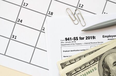 IRS Form 941-SS Employers quarterly federal tax return blank lies with pen and many hundred dollar bills on calendar page. Tax period concept. Copy space for text
