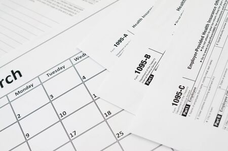 IRS Form 1095-A 1095-B and 1095-C blank lies on empty calendar page. Tax period concept. Copy space for text 写真素材
