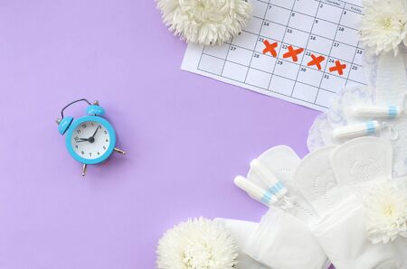 Menstrual pads and tampons on menstruation period calendar with blue alarm clock and white flowers. Aspects of women wellness in monthlies period. Woman critical days gynecological menstruation cycle