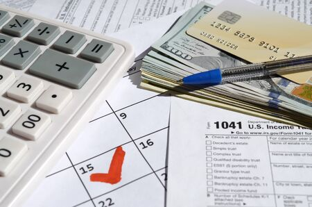 1041 Income Tax Return for Estates and Trusts blank with dollar bills, calculator and pen on calendar page with marked 15th April. Tax period concept. IRS Internal Revenue Service 写真素材 - 132116639