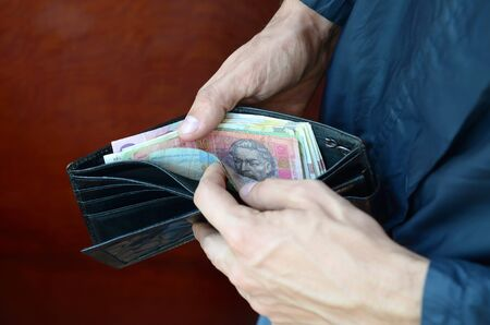 Close up male hands opened the wallet or purse with ukrainian money currency hryvnia. Salary in Ukraine. Big amount of money