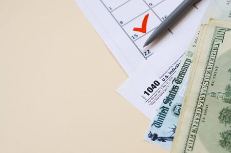 1040 Individual Income tax return form with Refund Check and hundred dollar bills on calendar with mark on 15th of april. Tax period concept. Financial planning and business 写真素材 - 132116827