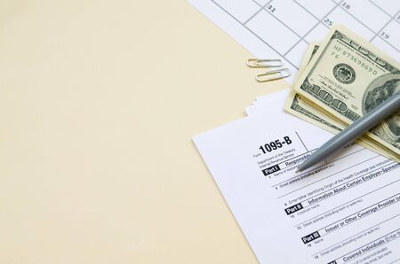 IRS Form 1095-B Health Coverage tax blank lies with pen and many hundred dollar bills on calendar page. Tax period concept. Copy space for text 写真素材
