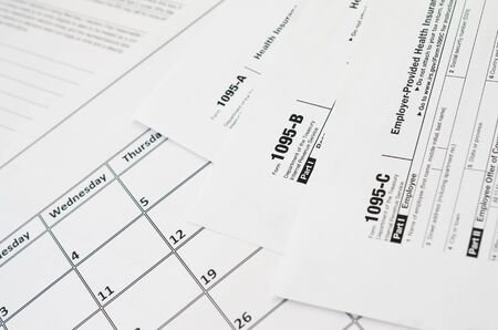 IRS Form 1095-A 1095-B and 1095-C blank lies on empty calendar page. Tax period concept. Copy space for text 写真素材 - 132116846